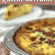 quiche lorraine in a pie plate next to a slice on a plate