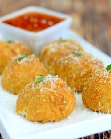 plate with 6 air fryer arancini and dipping sauce