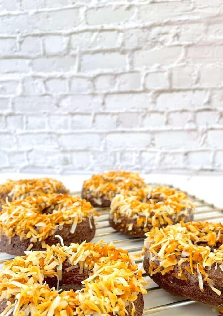 toasted coconut doughnuts on a cooling rack
