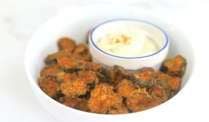 dill pickles in bowl with dip