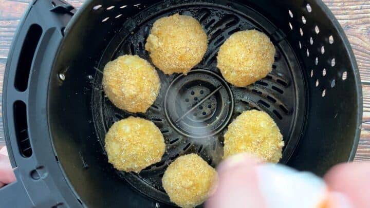 spraying arancini in air fryer basket
