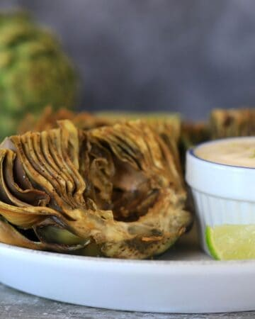 air fried artichokes ona plate with dipping sauce
