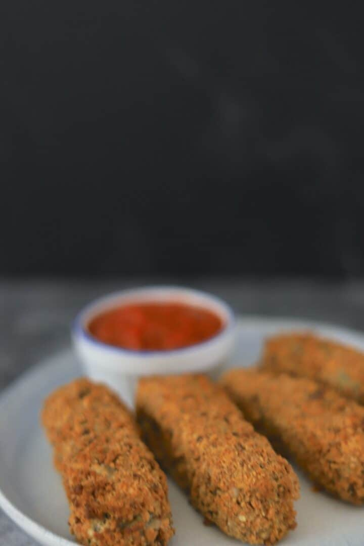 Mozzarella sticks on a plate with dipping sauce