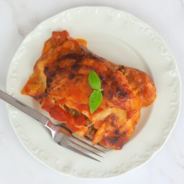 Lasagna on a plate with a fork and basil leaves on top