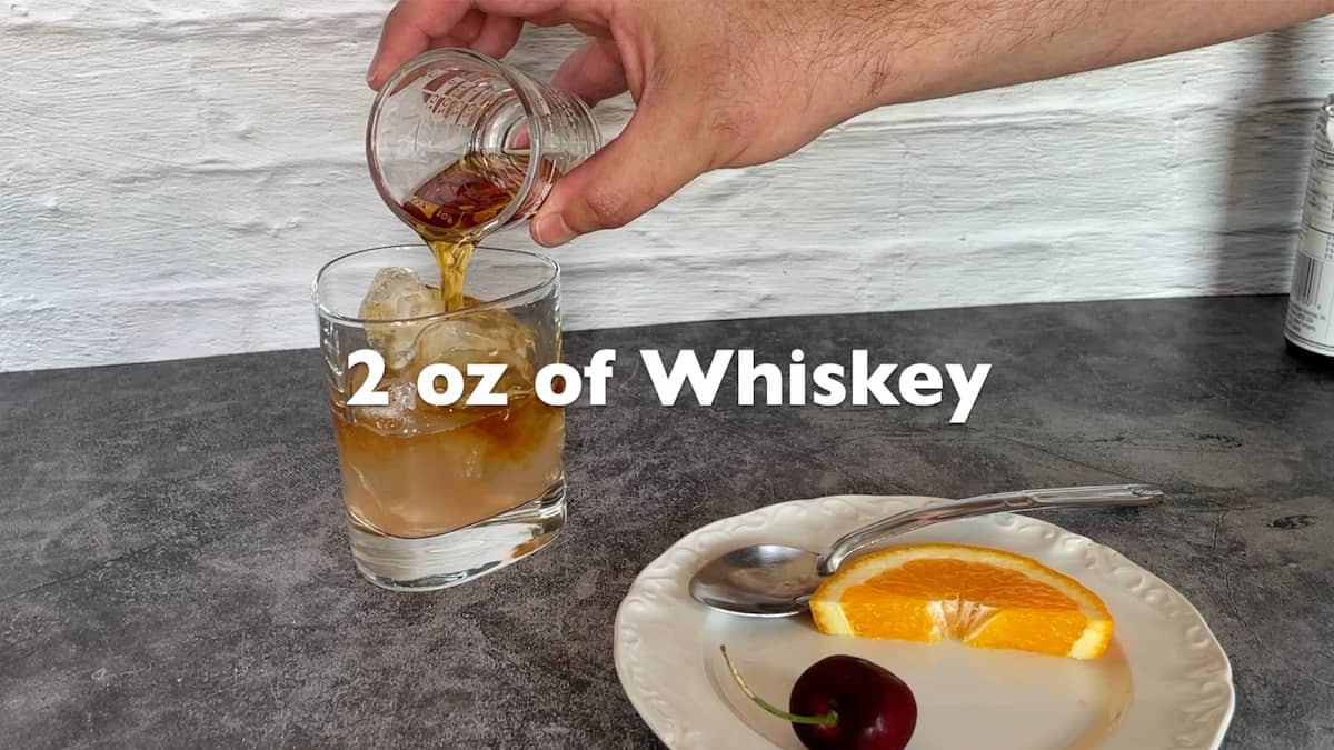 adding the whiskey to the glass
