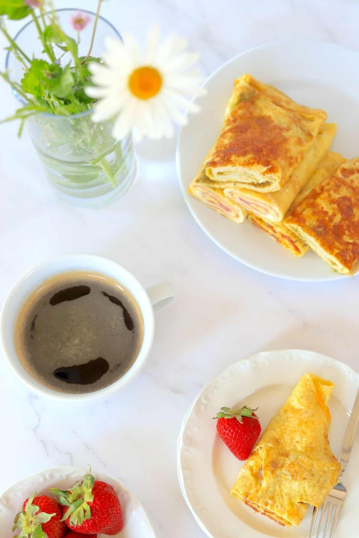 low carb roll ups on a plate with coffee, flowers and strawberries