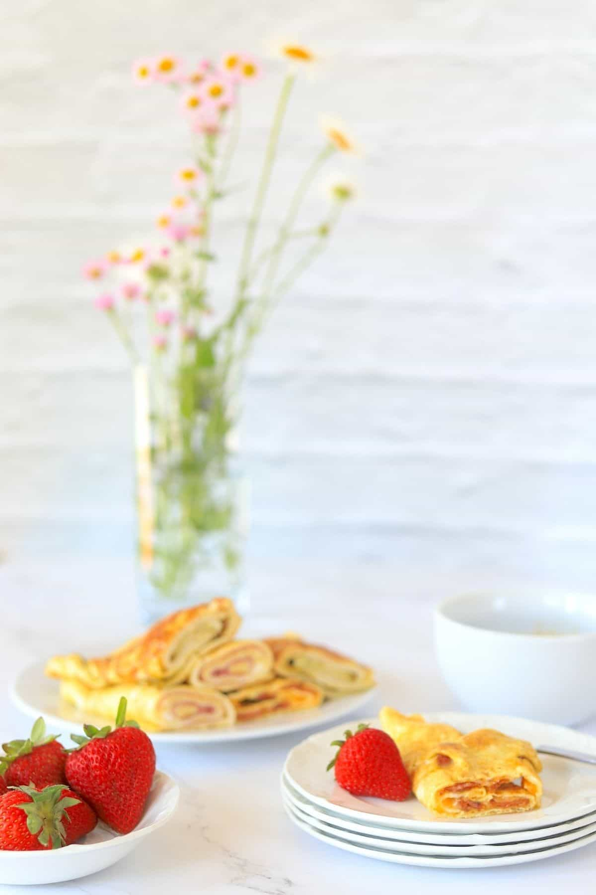 Low Carb Egg Rolls Ups on a plate with vase of flowers and a coffee and strawberries