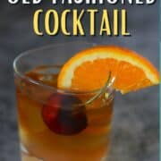 old fashioned cocktail in a tumbler with an orange wedge and cherry