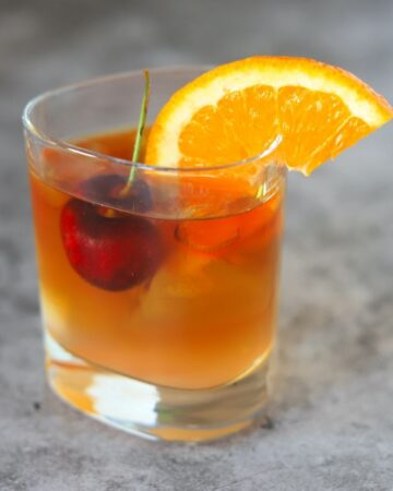 old fashioned cocktail with a cherry and orange wedge in a tumbler