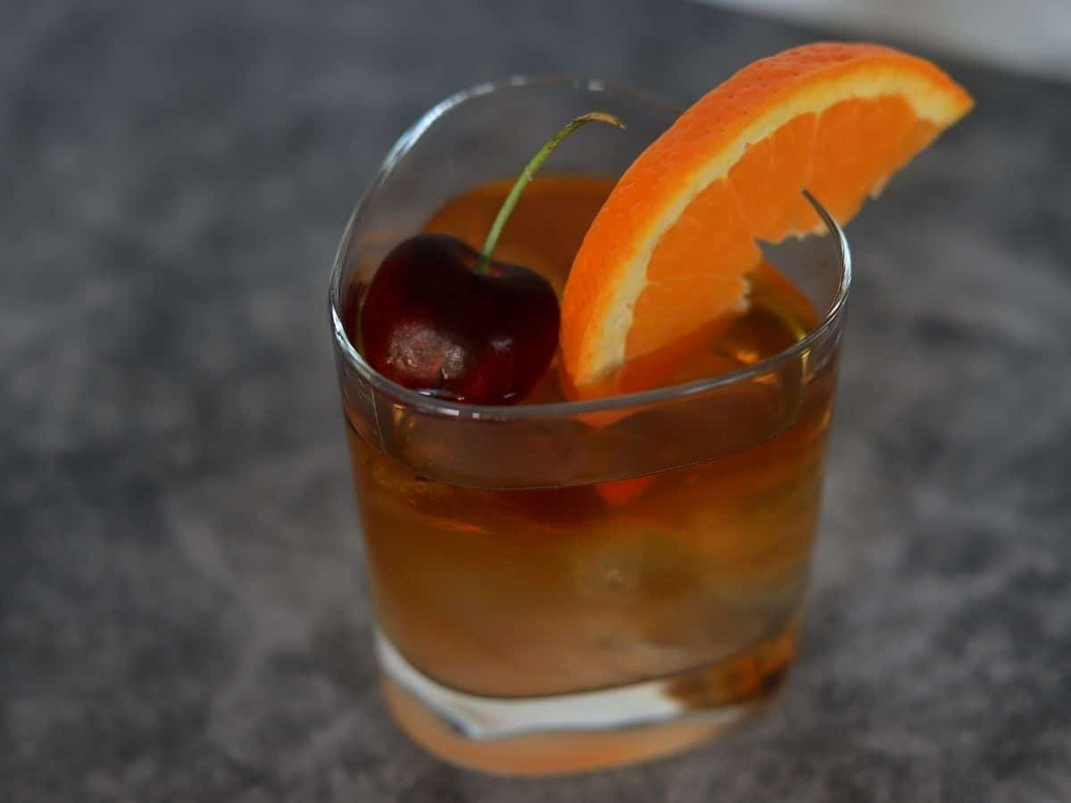 Tumbler filled with an old fashioned cocktail topped with orange wedge and cherry