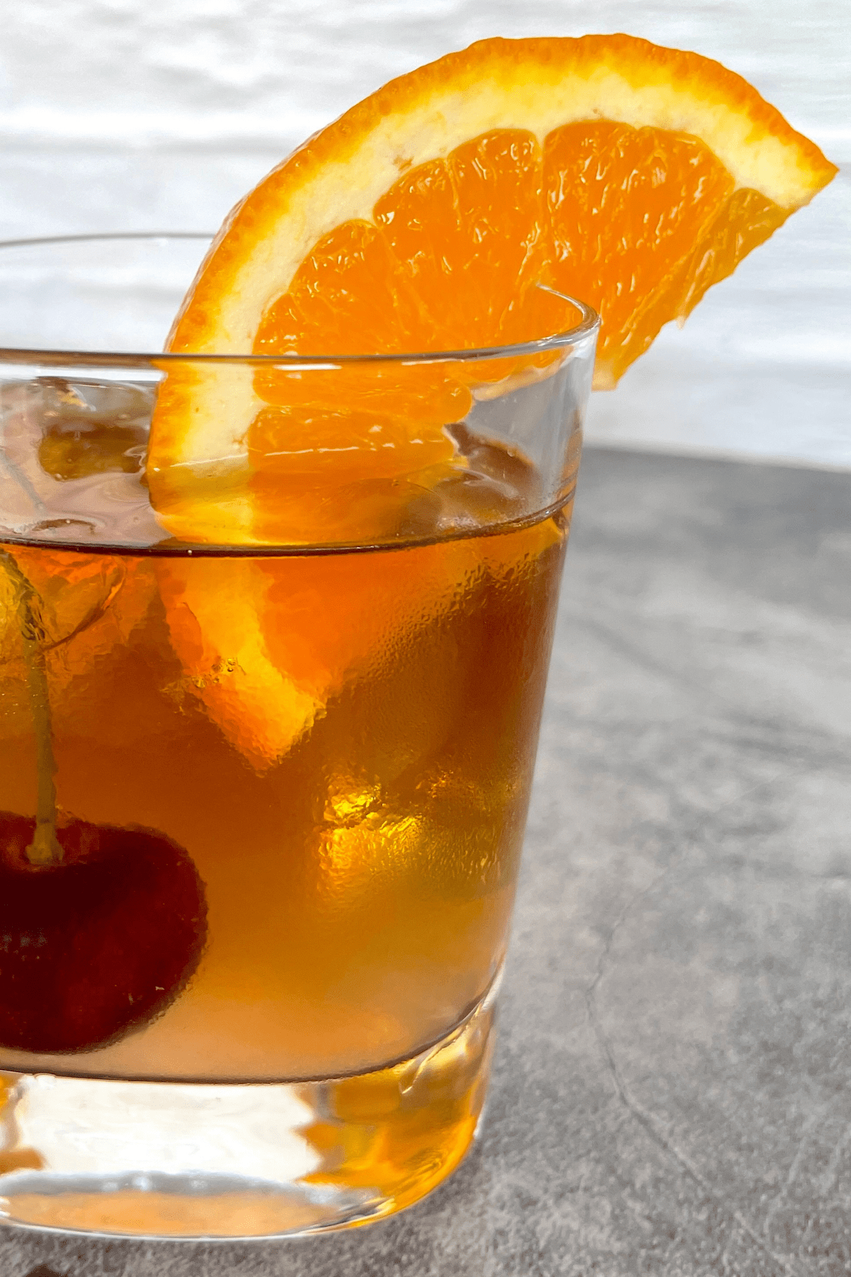 Old fashioned cocktail with an orange wedge and cherry