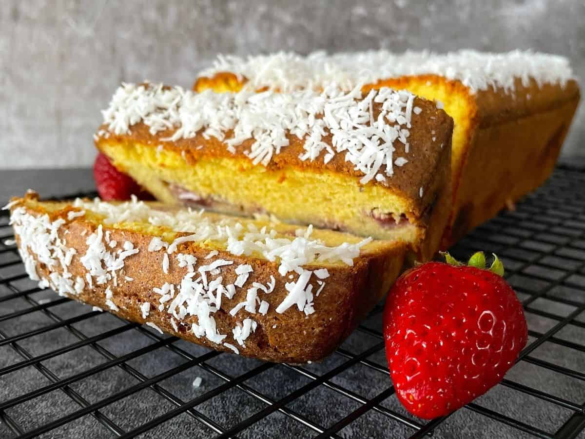 pound cake on cooling rack with fresh strawberries
