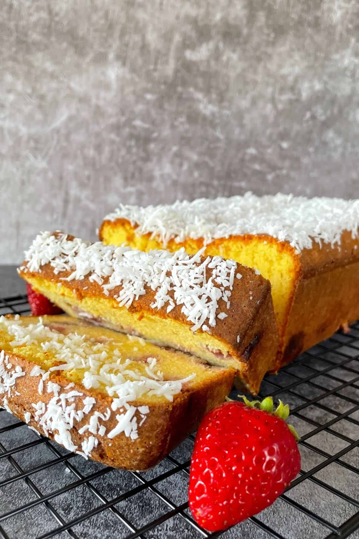 Strawberry pound cake on a cooling rack with fresh strawberries