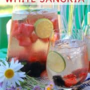 a glass and pitcher of white sangria on a table outdoors with a daisy