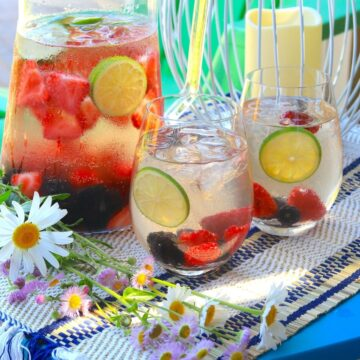 a pitcher of sangria with two glasses outdoors with flowers