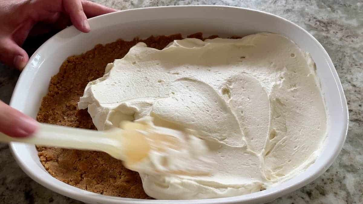 spreading cream cheese mixture over the crumbs