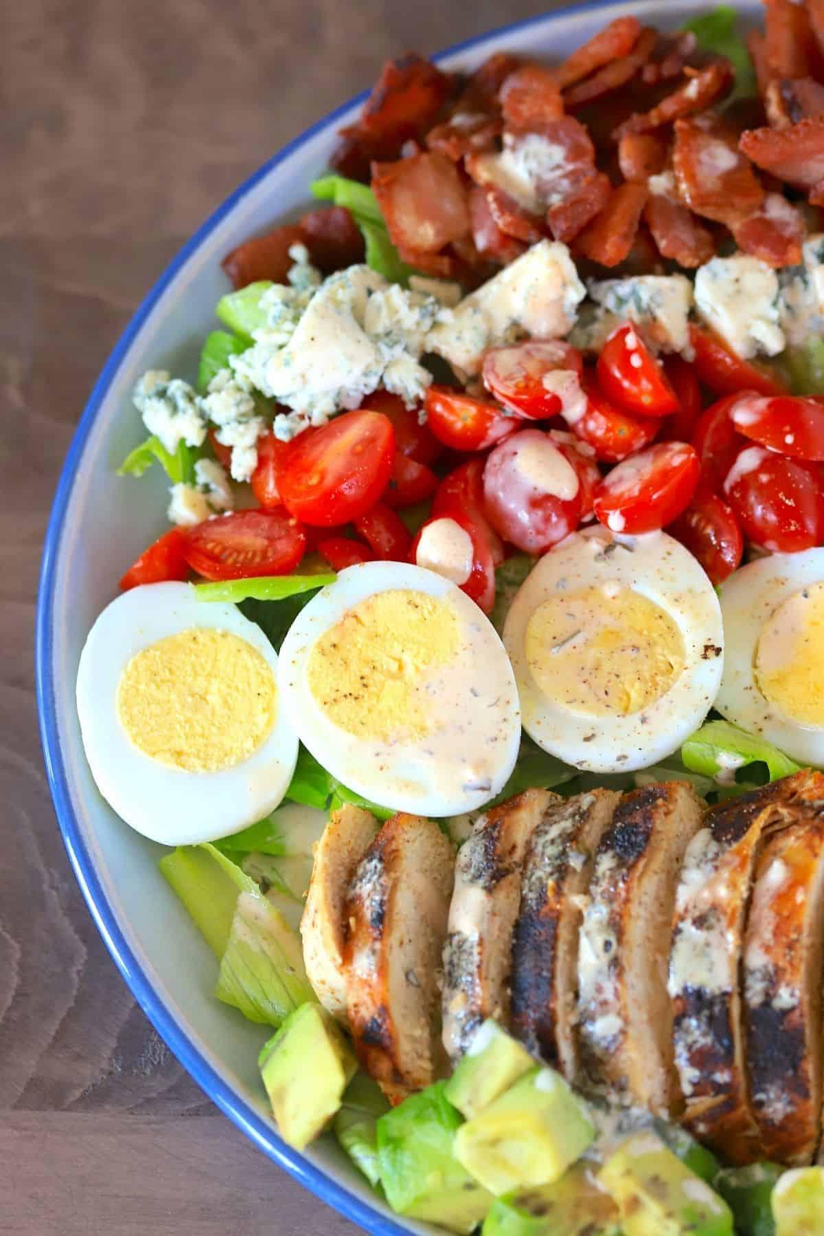 cobb salad on a blue rimmed plate