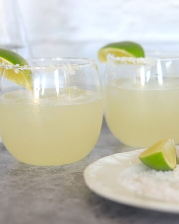 two glasses of margarita with lime wedges