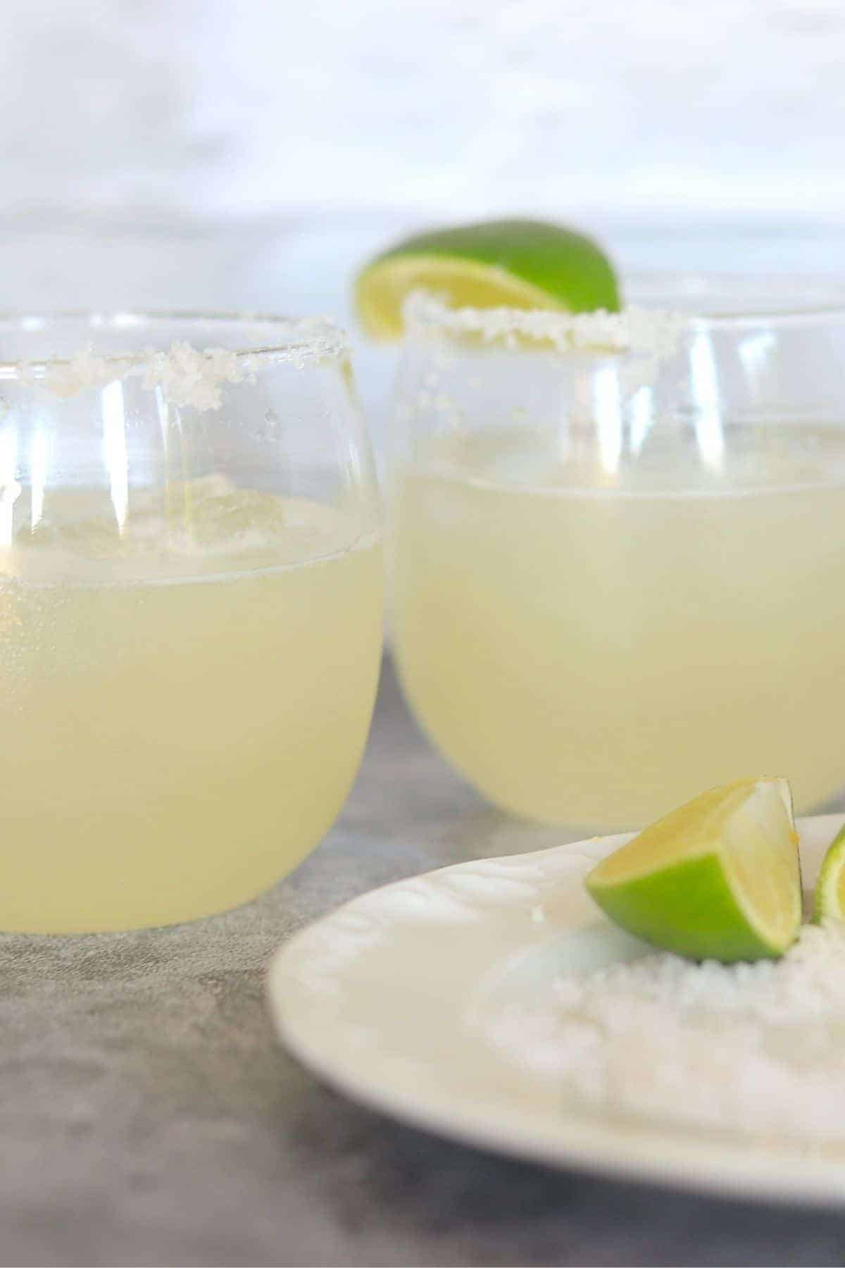 2 glasses filled with Margarita Low Carb Sugar Free and a plate with lime and salt