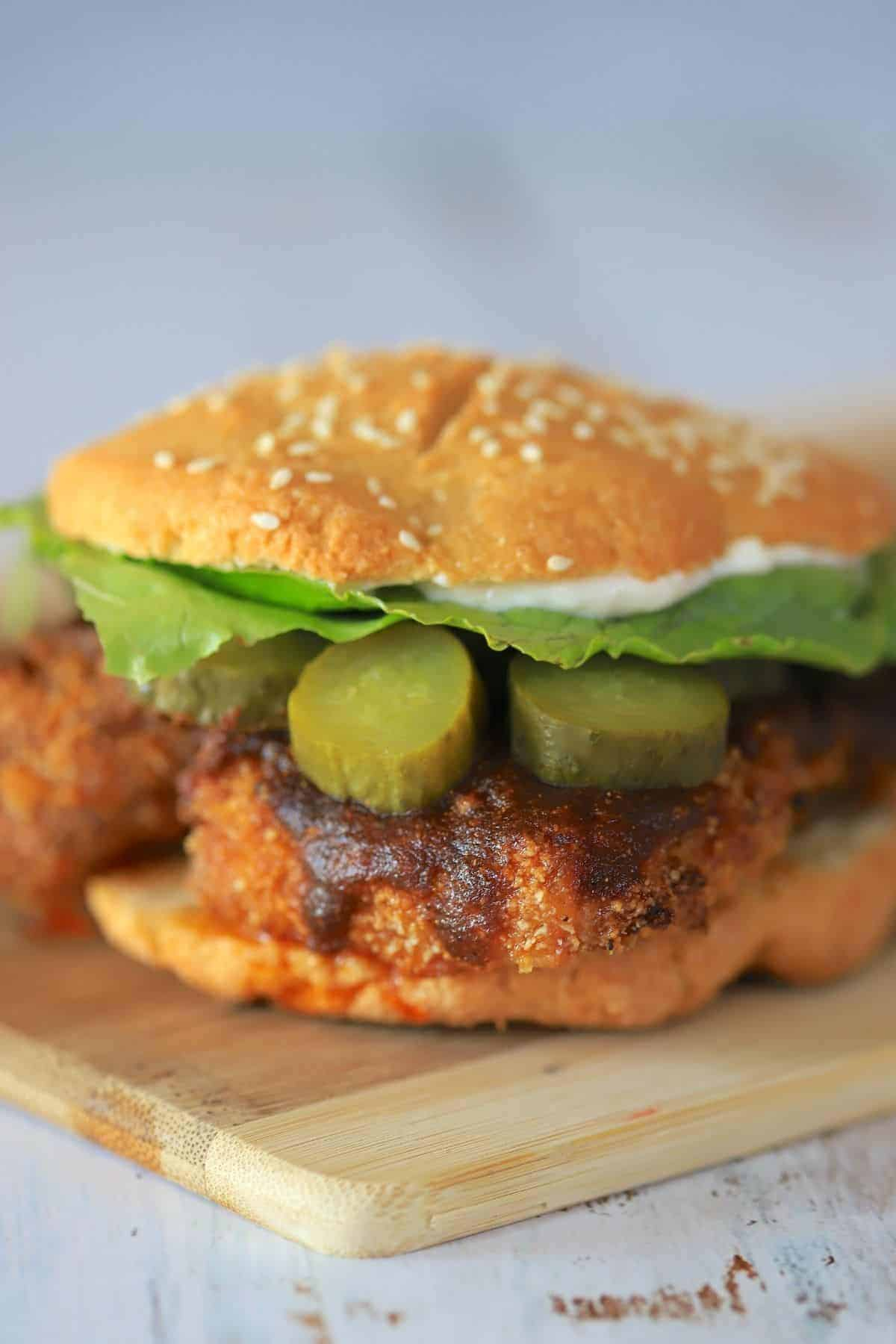 nashville hot chicken sandwich on a cutting board