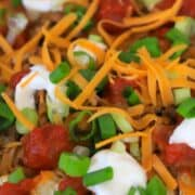 Cauliflower nachos topped with taco meat, salsa, sour cream and green onions