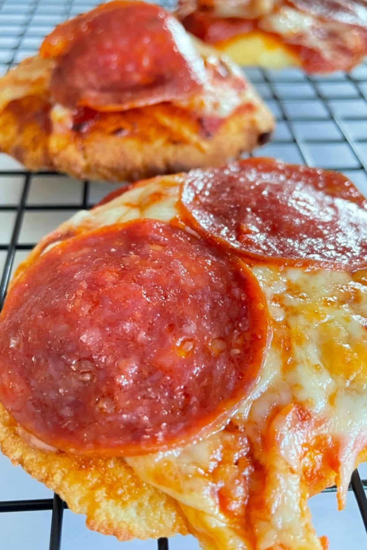 3 mini pizzas topped with cheese and pepperoni on a cooling rack