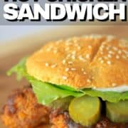 nashville hot chicken sandwich on a cutting board with pickles, lettuce and mayo