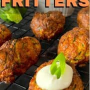 zucchini fritters on a cooling rack topped with sour cream and onion