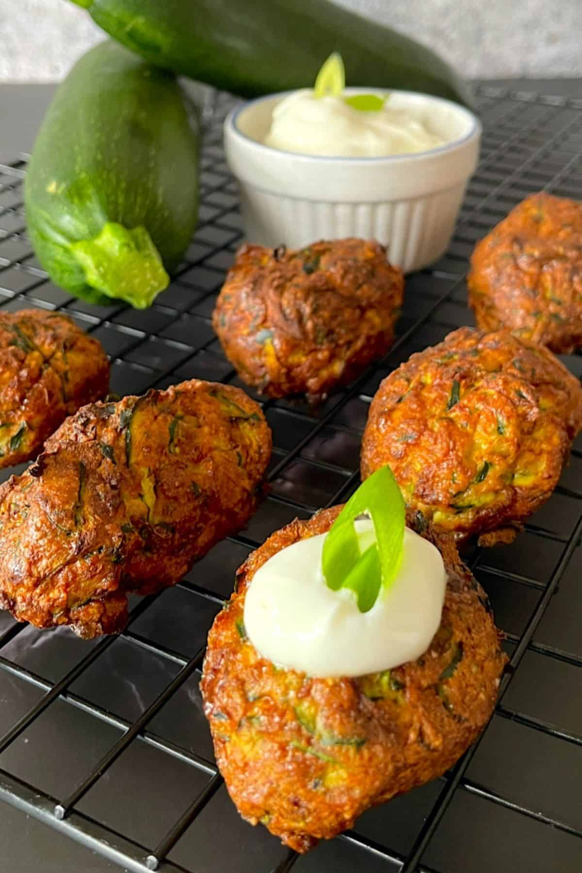 zucchini fritters on a cooling rack topped with sour cream and onion with a dipping bowl and two raw zucchinis