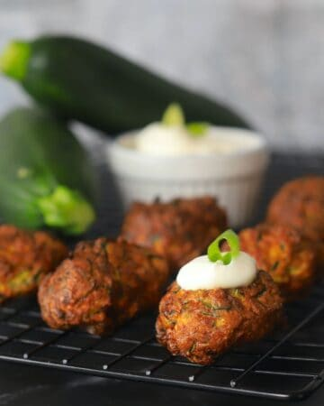 zucchini fritters on a cooling rack topped with sour cream and onion with a dipping bowl and 2 raz zucchinis