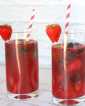 2 tall glasses filled with berry daiquiris a straw and garnished with a strawberry