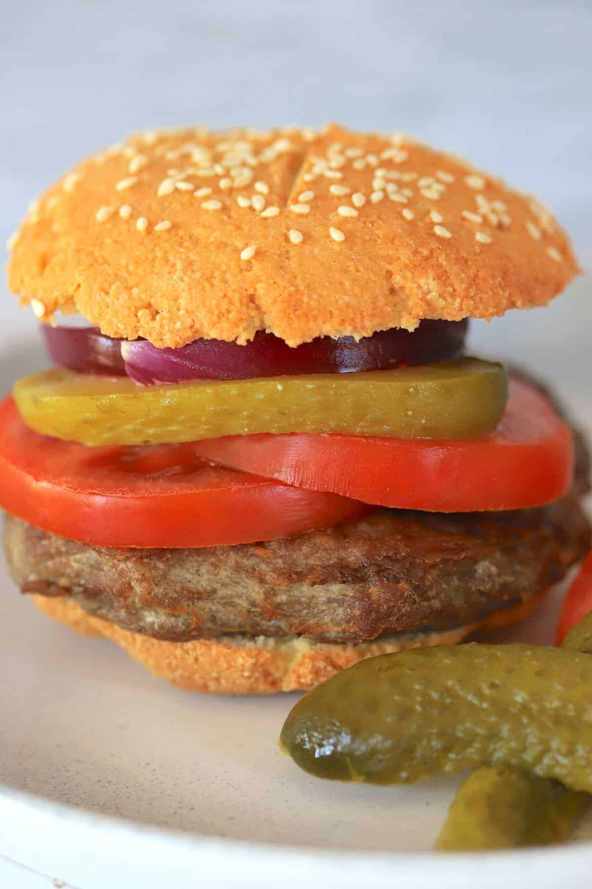 hamburger with bun on a plate with tomatoes onion and pickles