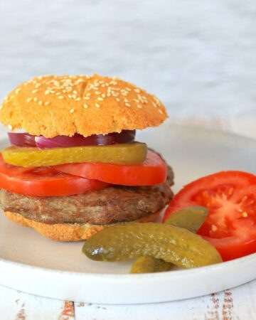 Hamburger on a plate filled with tomatoes onion and pickles with a side of pickles and tomatoes