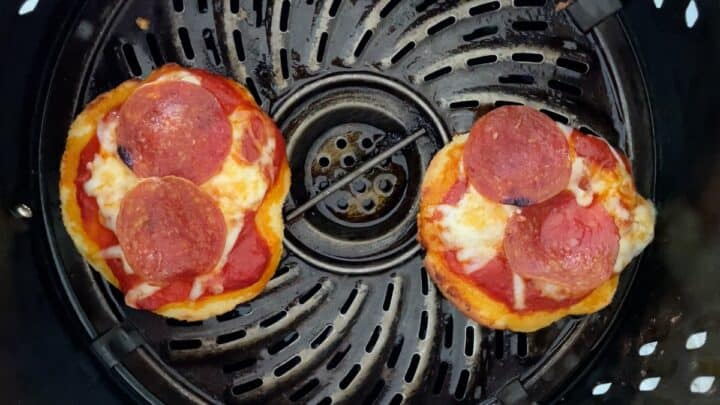 Two mini pizzas cooked in the air fryer basket
