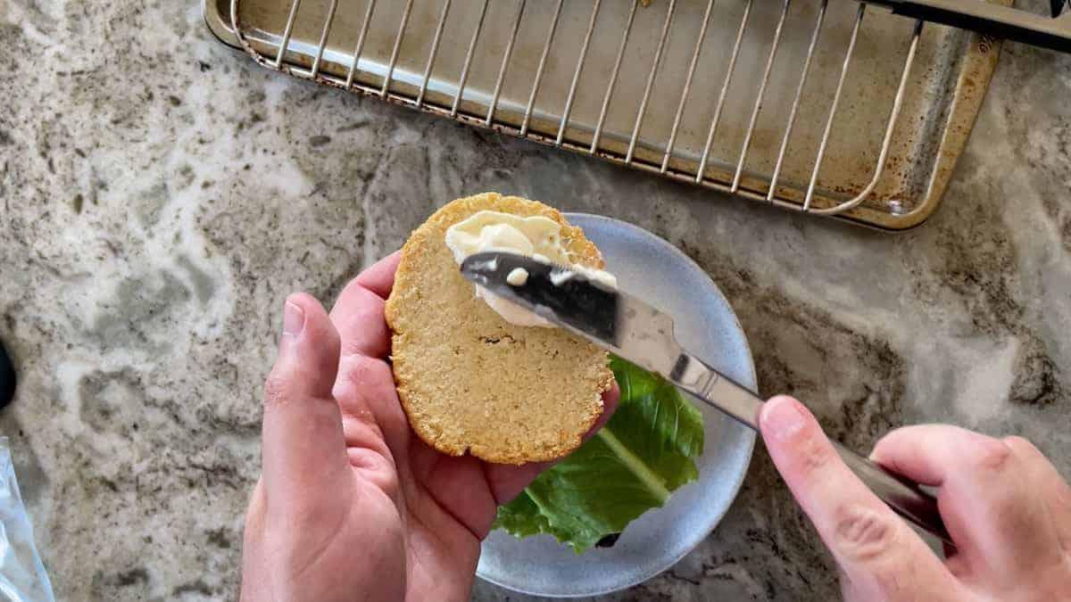 spreading butter onto the bottom of a burger bun