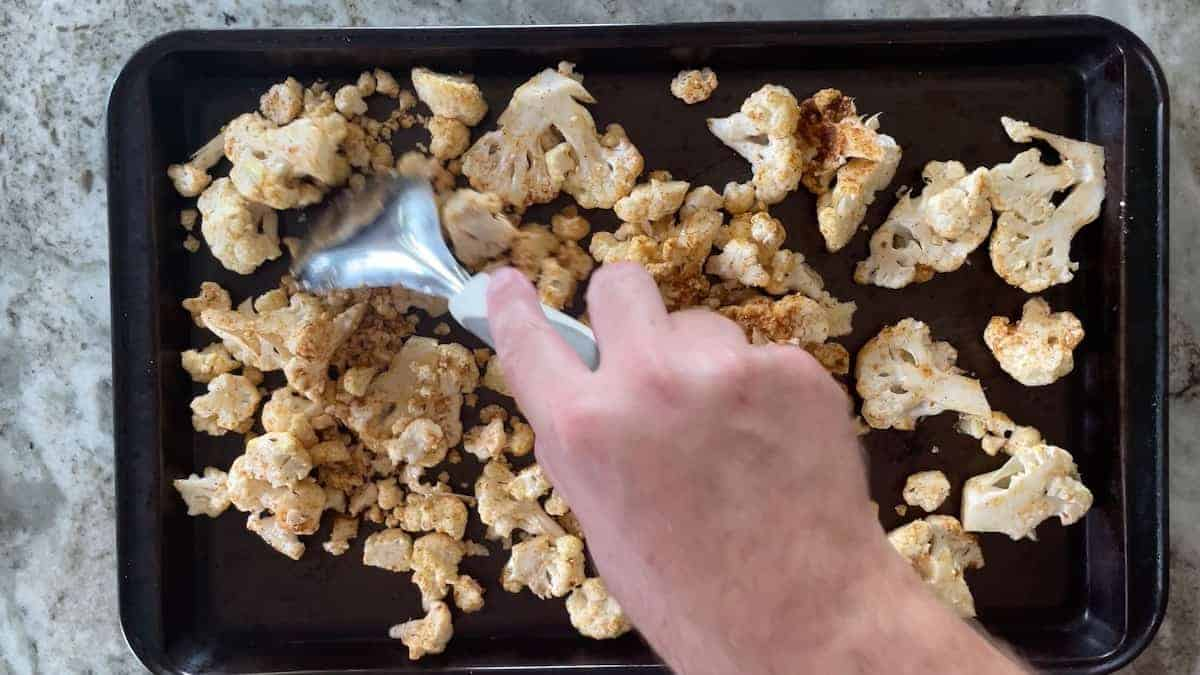 adding cauliflower to a sheet pan