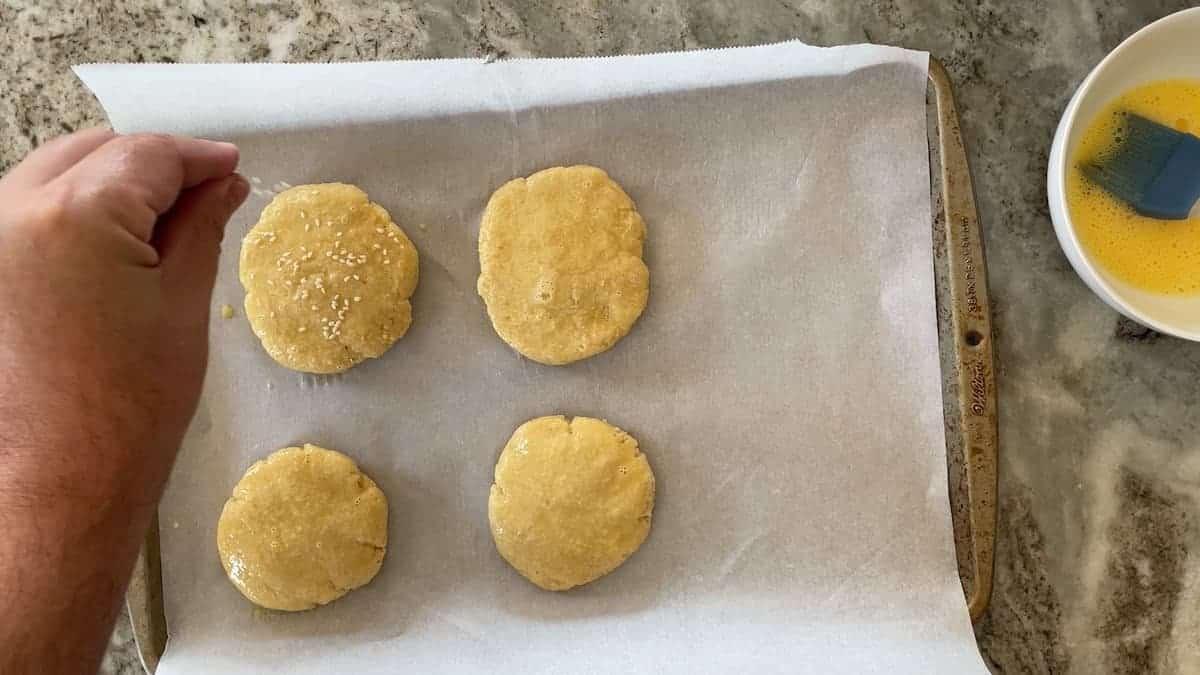 4 hamburger buns on a parchment lined baking sheet