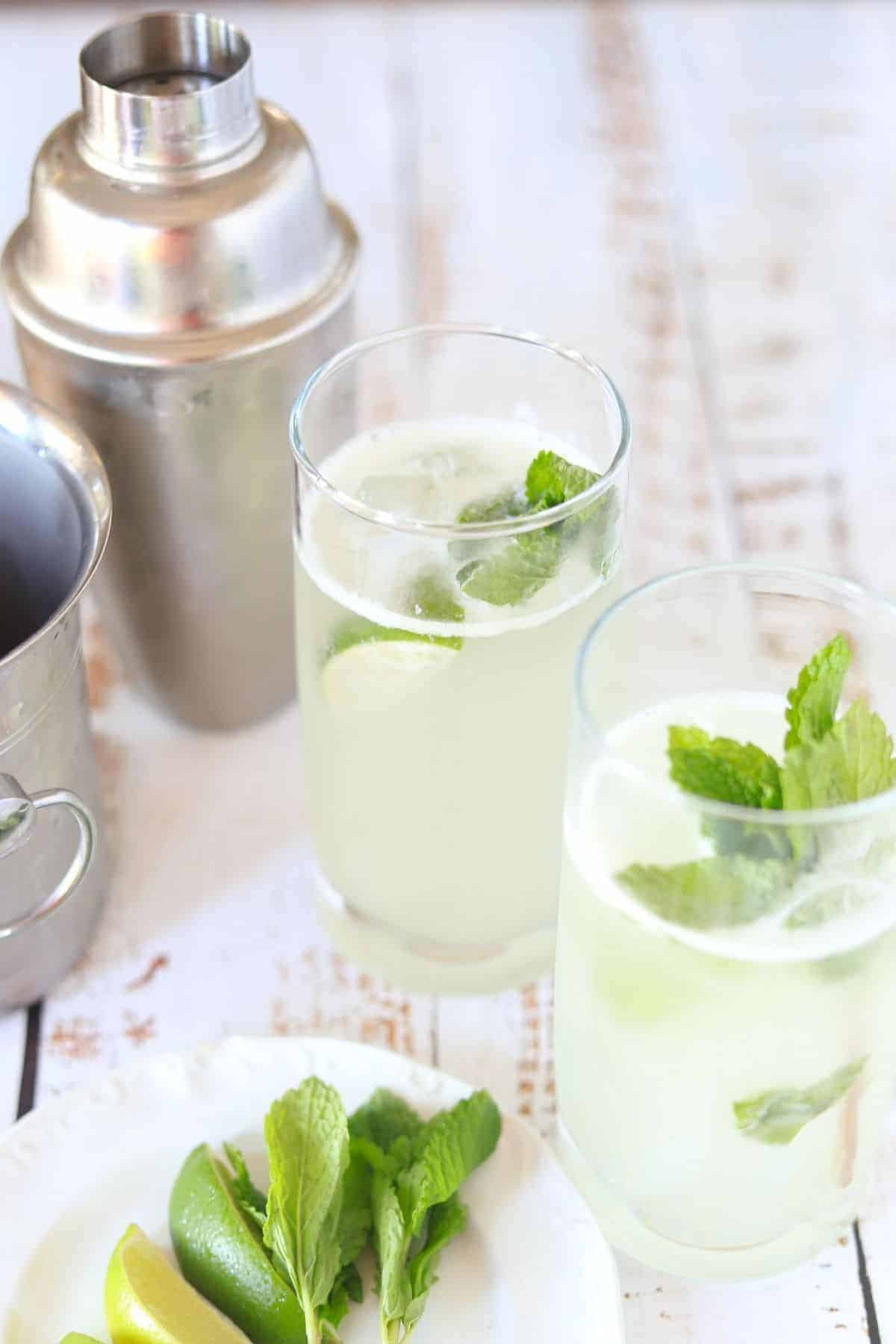 2 glasses filled with mojito lime wedge and sprig of mint