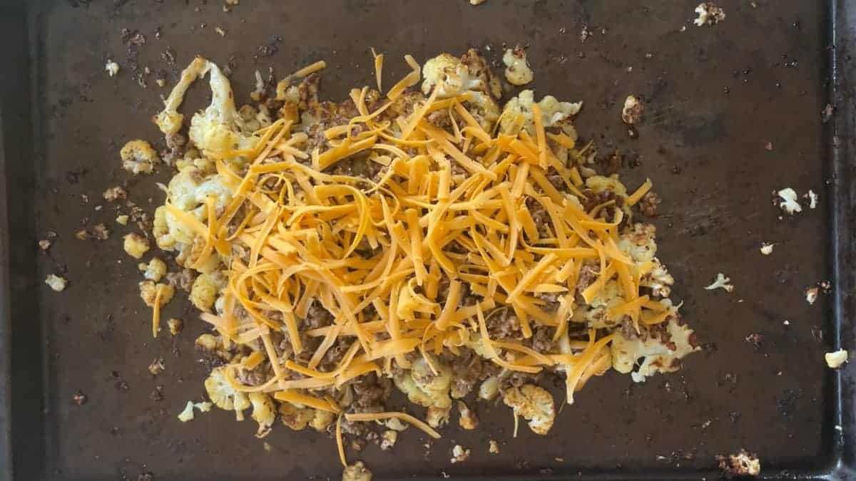 cauliflower in centre of sheet pan topped with taco meat and shredded cheddar cheese