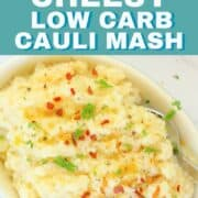 cauliflower mash in a bowl with a spoon topped with chili flakes, olive oil and parsley