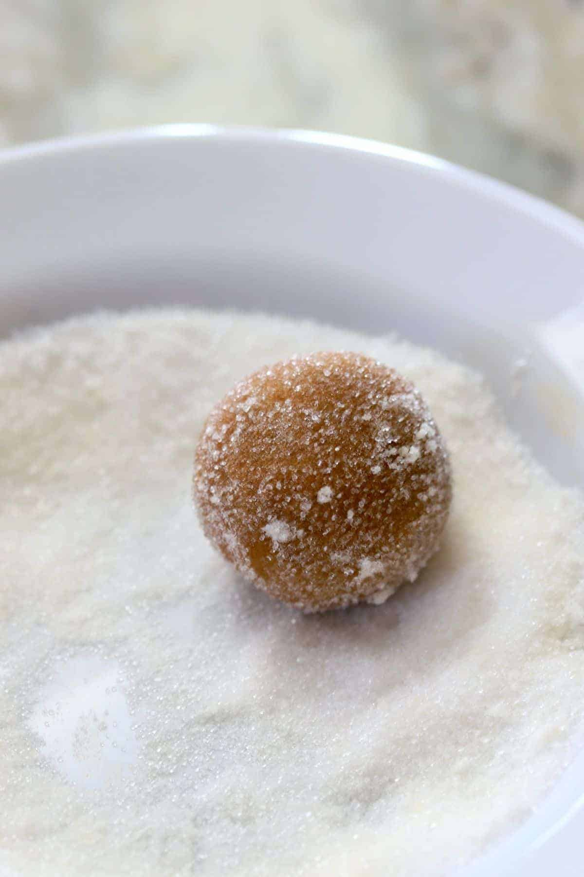 cookie dough ball coated in sugar in a sugar bowl
