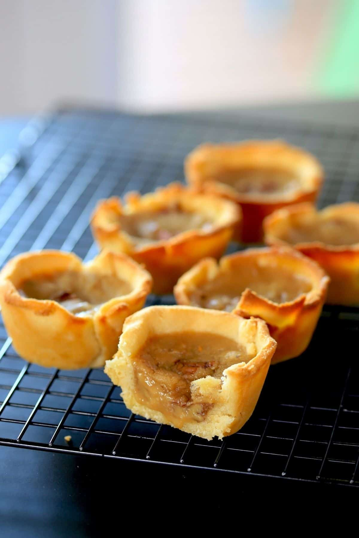 6 golden butter tarts with one sliced to show the gooey filling