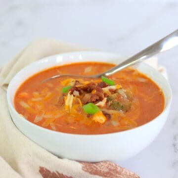 Bowl of cheeseburger soup with a spoon in it