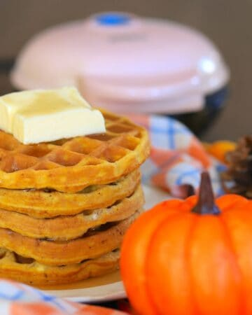 a stack of waffles topped with a pad of butter next to a mini pumpkin and a waffle iron