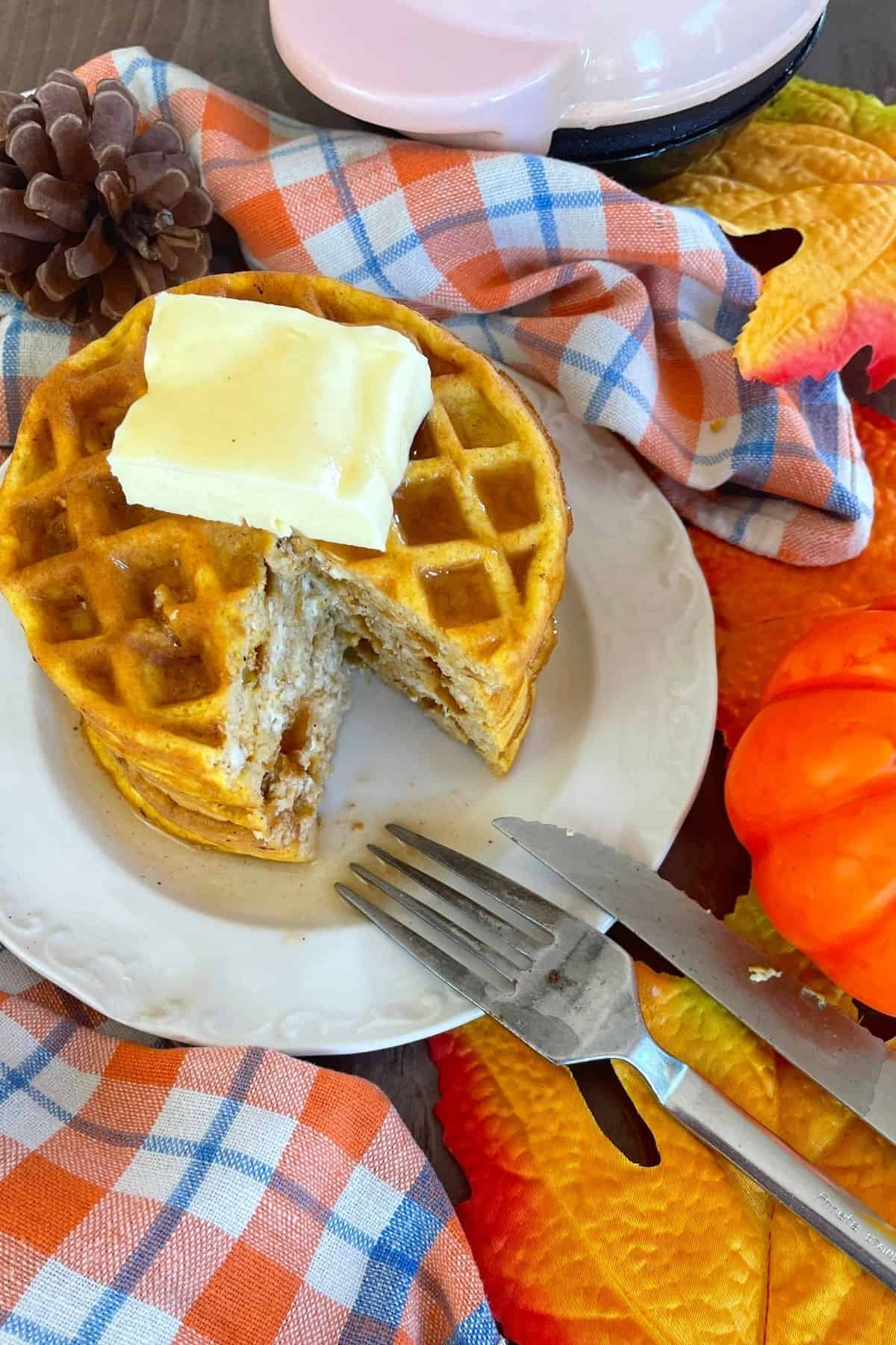 stacked waffles on a plate with a fork and knife, next to a mini pumpkin and the dash waffle iron
