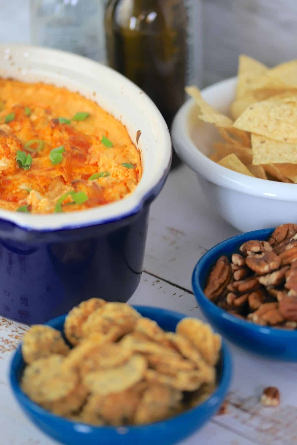 casserole of buffalo dip with bowls of nacho chips pecans and cheese crackers and a tv remote