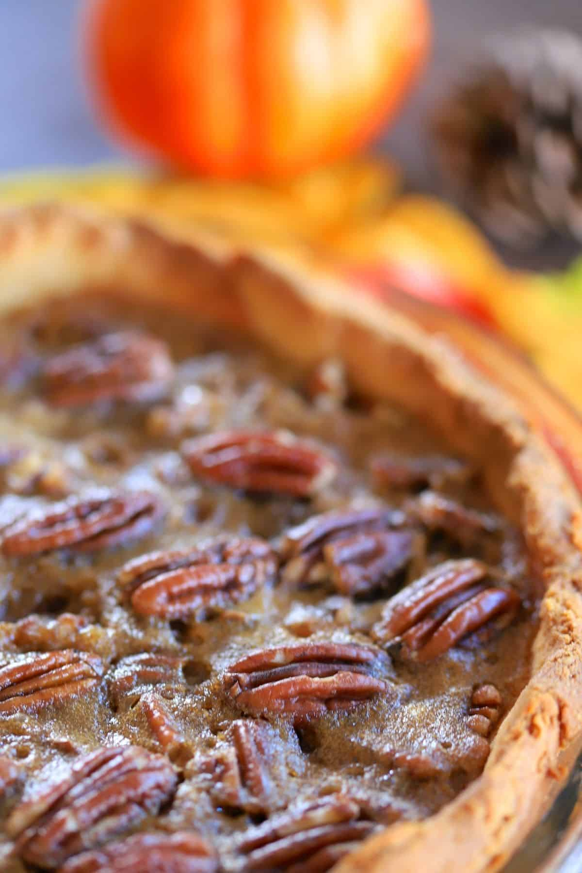 pecan pie with a pumpkin ornament and yellow leaves