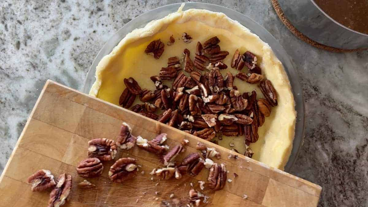 cutting board with pecans and a pie crust with pecans in them