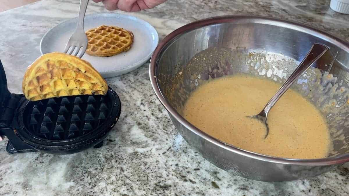 lifting a waffle out of the iron with a fork