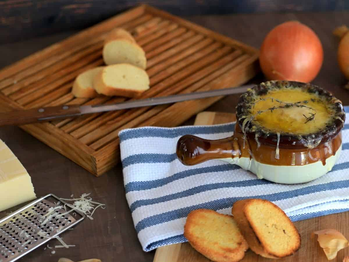 bowl of french onion soup topped with a sprig of time next to crusty bread, cheese and onions
